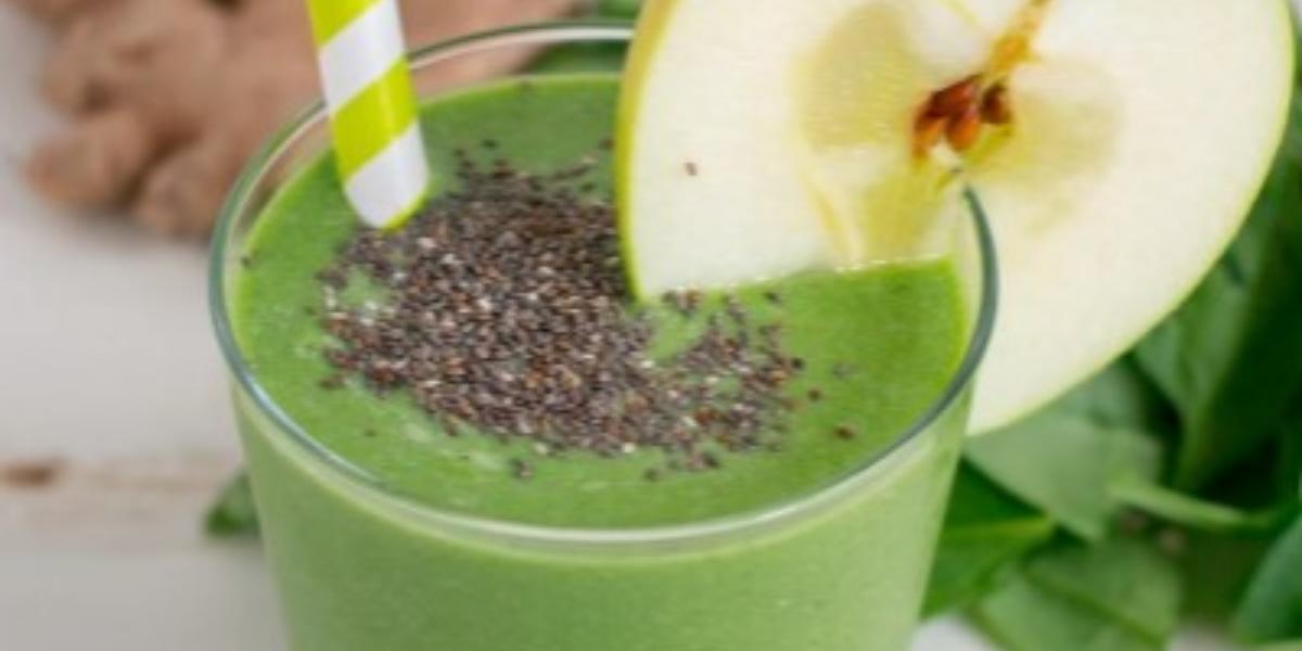 Fotografia em tons de verde em uma mesa branca com um copo de vidro alto e o smoothie de maçã verde com banana e chia dentro dele, com uma fatia de maçã enfeitando o copo. Ao fundo, folhas de espinafre e gengibre.