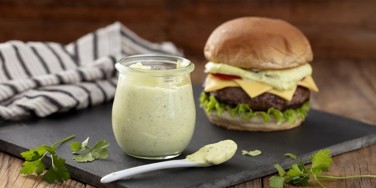Fotografia em tons de verde em uma bancada de madeira clara, um pano branco com listras pretas, uma tábua de ferro preta e em cima dela, um potinho de vidro com a maionese verde caseira e ao lado um hambúrguer para acompanhar essa deliciosa maionese.
