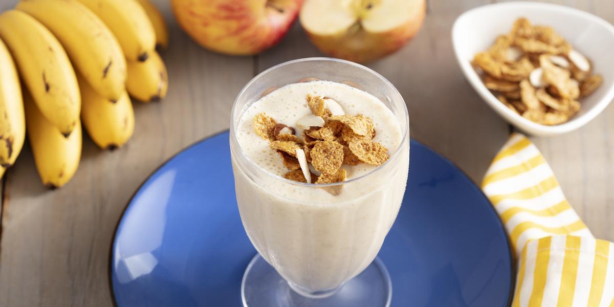 Imagem de um copo com a bebida cremosa em tom claro, decorado com cereal. Ele está sobre um prato azul e, ao redor, há cereais espalhados na mesa, uma penca de bananas, duas maçãs e um tecido listrado amarelo e branco.