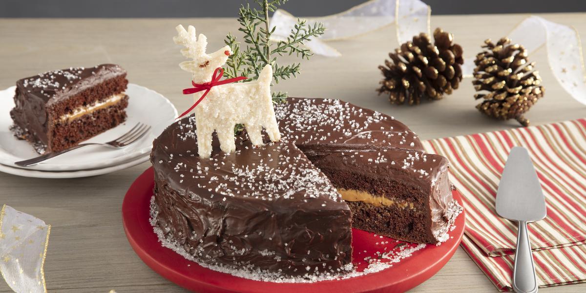 Fotografia em tons de vermelho em uma bancada de madeira clara, um pano bege com listras vermelhas, um prato vermelho redondo com o bolo de chocolate com recheio de doce de leite com decoração de natal. Ao fundo, um prato com uma fatia do bolo.