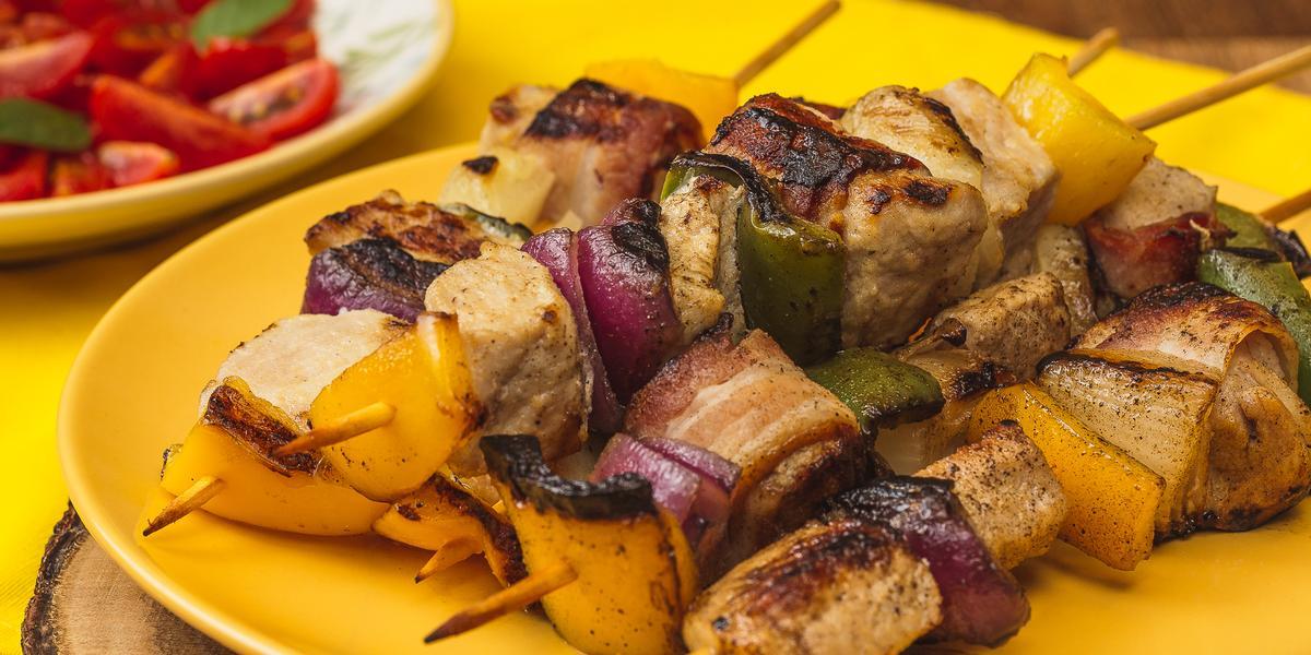 Foto bem aproximada de um prato amarelo sobre o qual há quatro espetinhos montados com carne de porco, cebolas roxa e tradicional e pimentões verdes e amarelos. Ao fundo há um prato branco com uma salada de tomates.