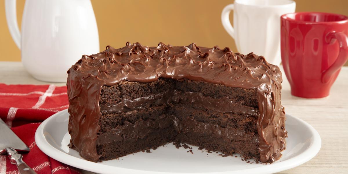 Fotografia em tons de vermelho em uma bancada de madeira com um pano vermelho listrado em branco, com um prato branco no centro com o bolo brownie com brigadeiro de cacau de cobertura. Ao fundo, uma xícara branca, uma xícara vermelha e um bule branco.