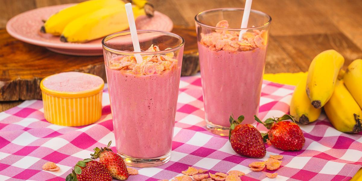 Imagem de uma bancada de madeira com um pano quadriculado em tom de rosa claro, morangos, e cereais espalhados, além de dois copos com uma bebida cor de rosa e canudos.