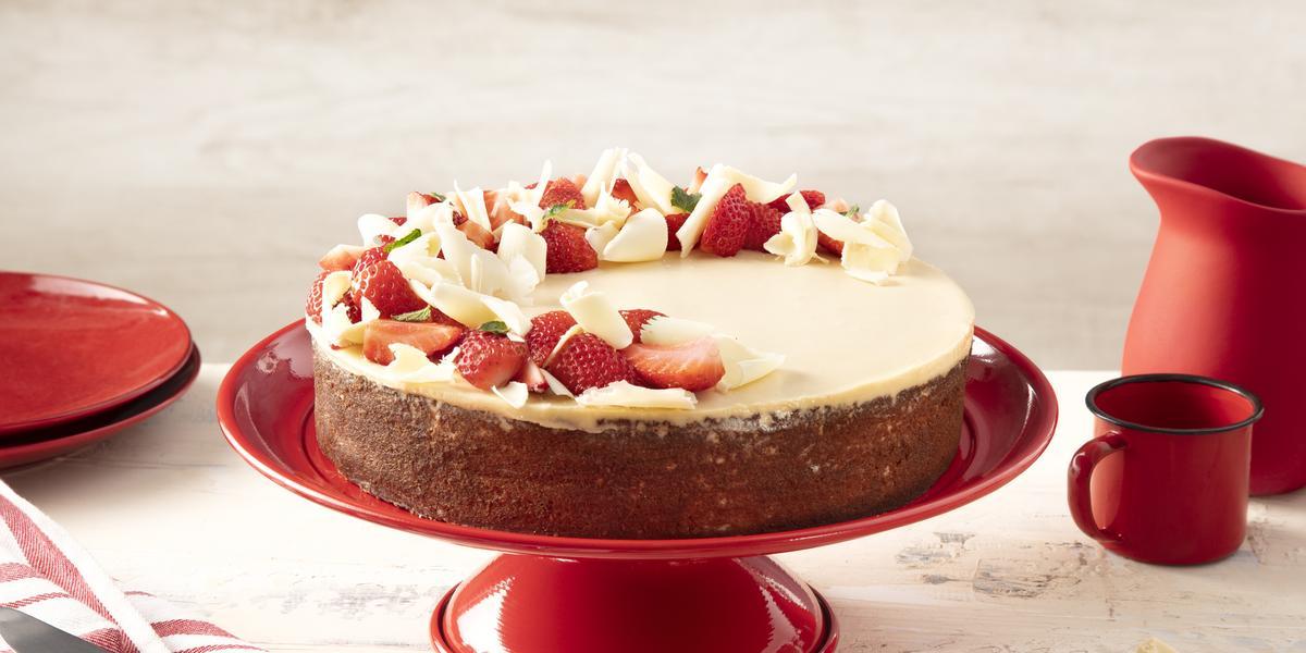 Fotografia em tons de vermelho em uma bancada bege com um paninho listrado branco e vermelho e ao centro um suporte vermelho com o bolo de três leites com ganache de chocolate branco. Ao lado, pedaços de chocolate branco, uma caneca e uma jarra vermelhas.