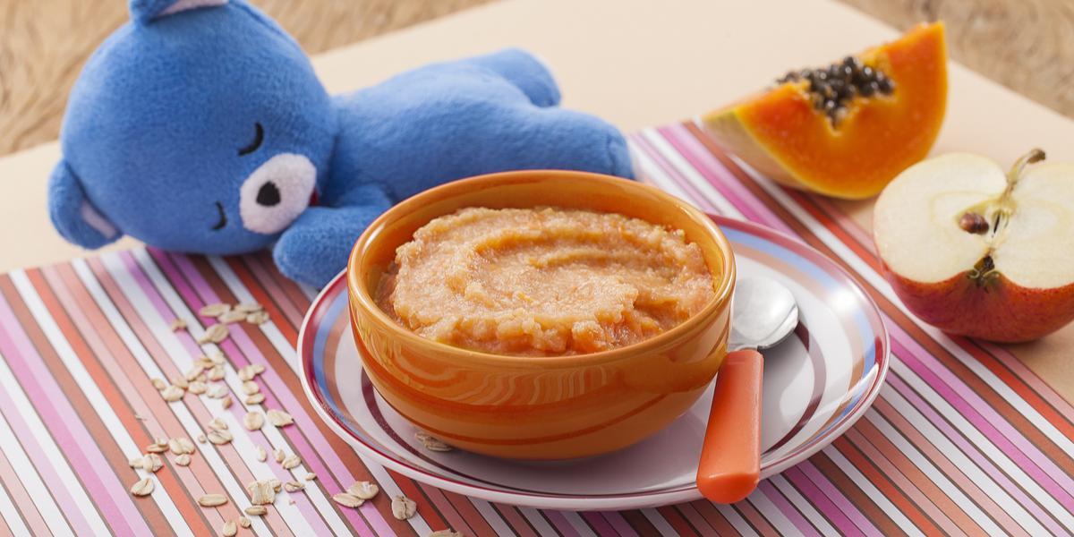 Fotografia em tons de laranja e azul de uma bancada de madeira com um paninho listrado colorido, um potinho laranja com o purêzinho de mamão, atrás um ursinho de pelúcia azul. Ao fundo, meio pedaço de maçã e meio pedaço de mamão.
