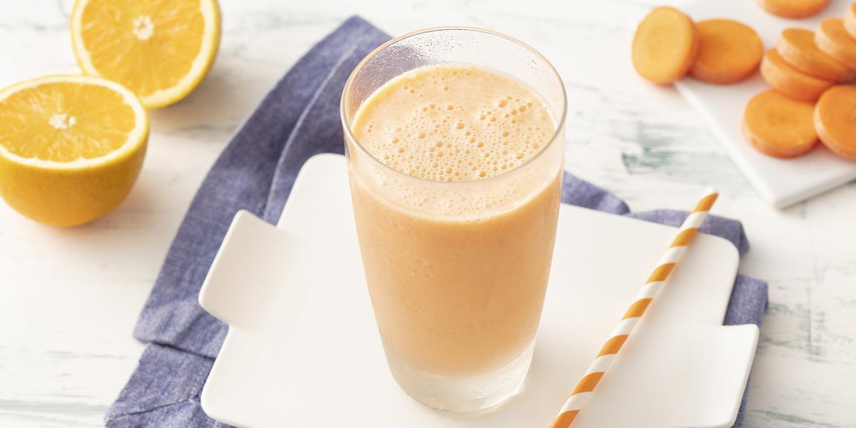 Fotografia em tons de laranja em uma bancada de madeira clara com um pano azul e uma tábua branca ao centro com um copo de vidro com a bebida refrescante de laranja e cenoura. Ao lado, um canudo listrado laranja, algumas fatias de cenoura e uma laranja.