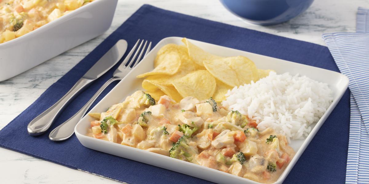 Fotografia em tons de azul em uma bancada de mármore branco com um jogo americano azul escuro, um prato quadrado branco grande com o strogonoff de legumes, arroz branco e batatas chips dentro dele. Ao fundo, um recipiente com mais strogonoff de legumes.