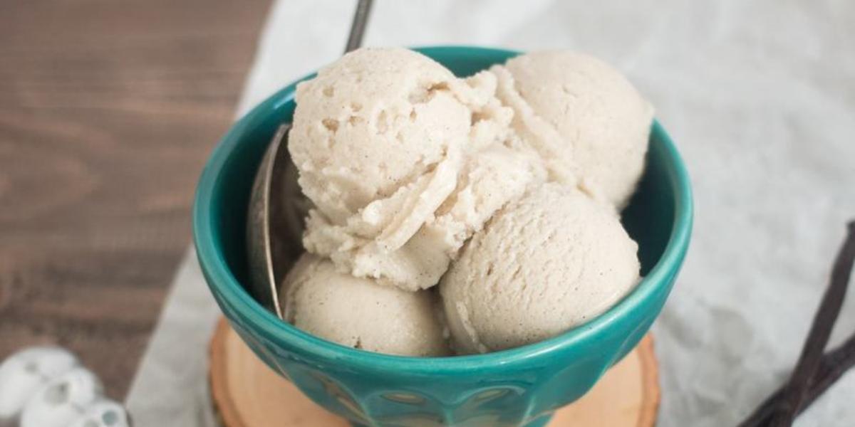 Fotografia em tons de verde em uma bancada de madeira com um pano branco amassado, um pote verde com o sorvete de baunilha e mel dentro. Ao lado, um pegador de sorvete com uma bola dentro dele.