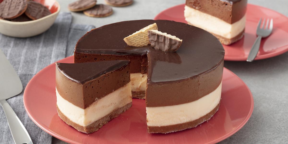 Fotografia em tons de vermelho em uma bancada de madeira cinza, um pano cinza listrado, um prato vermelho redondo raso com a torta mousse de chocolate com recheio de sorvete de creme e cobertura de chocolate.
