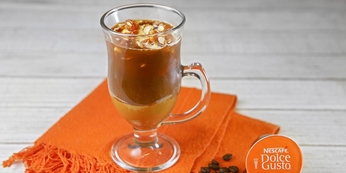 Fotografia em tons de laranja em uma bancada de madeira branca, um pano laranja, uma xícara de vidro com o café com sorvete e pé de moleque dentro dele. Ao lado, uma cápsula de café caseiro intenso Dolce Gusto.