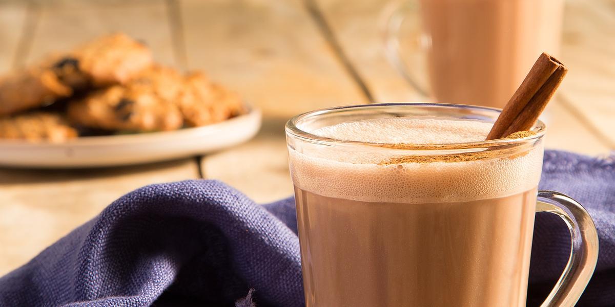 Fotografia em tons de marrom em uma bancada de madeira com um pano azul e duas xícaras de vidro com o chocaccino e um pau de canela para enfeitar. Ao fundo, um prato com cookies
