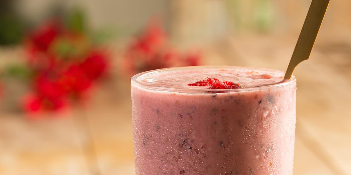 Fotografia em tons de rosa em uma mesa de madeira com um copo de vidro ao centro com o shake de frutas vermelhas dentro. Morangos e mirtilos espalhados pela mesa.