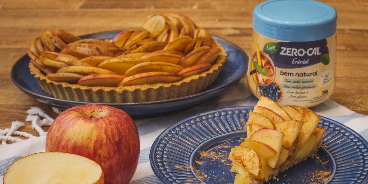 Fotografia em tons de vermelho em uma bancada de madeira escura, um pano com listras azuis, um prato azul ao centro com uma fatia da torta de maçã com aveia. Ao fundo, um prato maior com a torta inteira e um pote de adoçante Zero-Cal. Ao lado, maçãs.