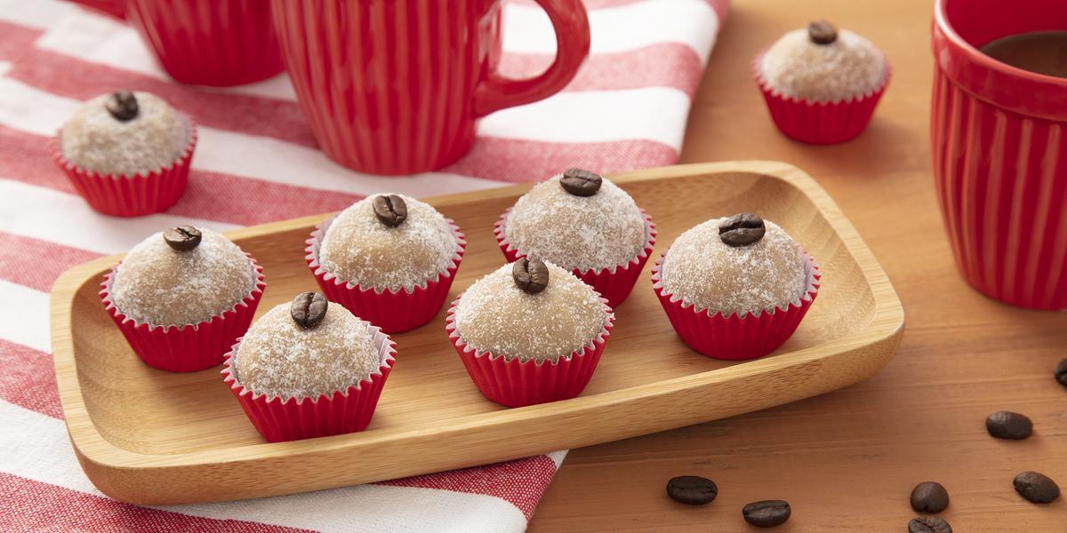 Fotografia em tons de vermelho de uma bancada de madeira, ao centro um pano listrado vermelho e branco e uma bandeja de madeira com seis brigadeiros em forminhas vermelhas, em cima de cada um deles um grão de café.