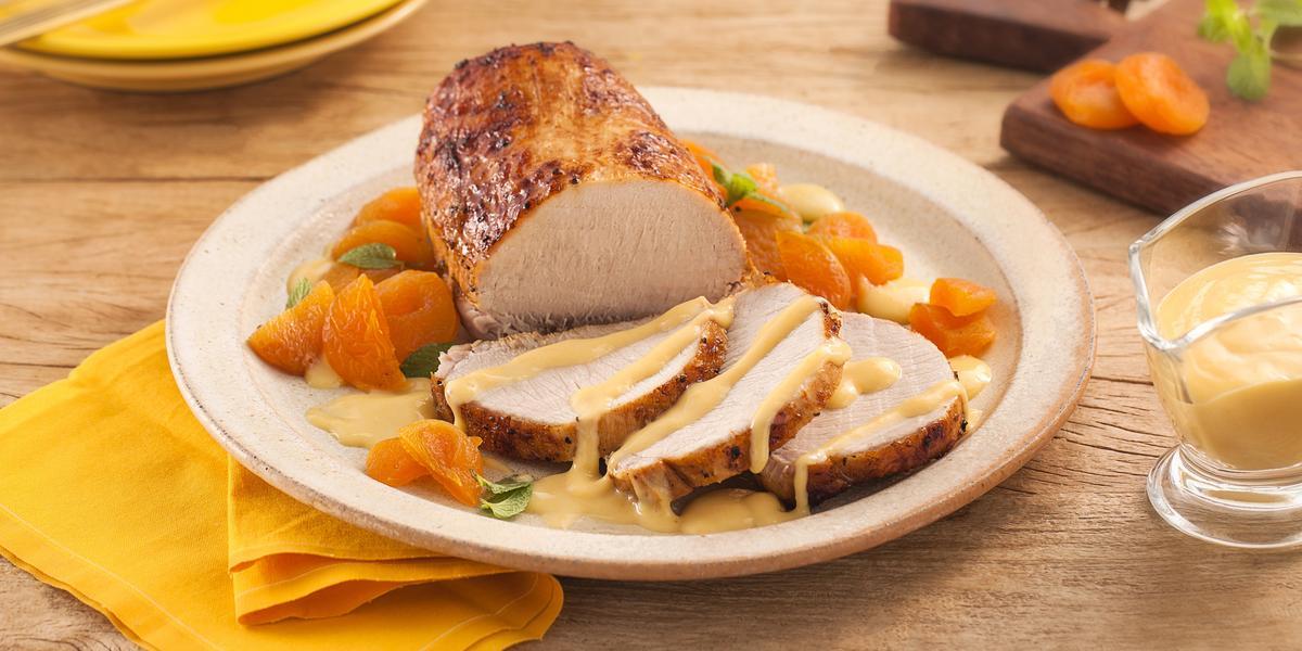 Fotografia em tons de amarelo em uma bancada de madeira clara, um paninho amarelo, um prato redondo bege com o lombo assado coberto com molho de damasco e decorado com folhas de hortelã. Ao lado, um potinho com o molho e uma tábua de madeira com damascos.