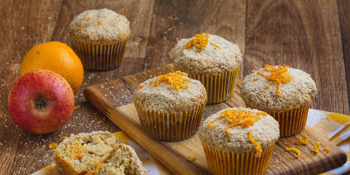 Imagem aproximada de muffins em tom claro, sobre uma tábua de madeira em um pano quadriculado em tom amarelo e branco. Ao fundo há uma maçã e uma laranja e alguns farelos de Farinha Láctea.