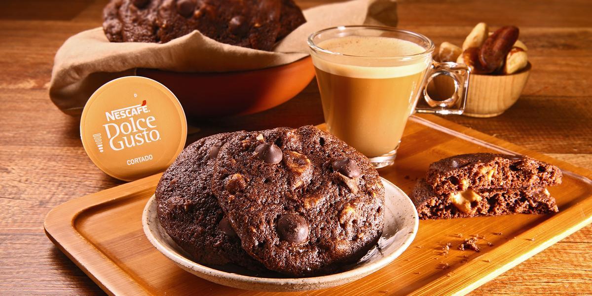 Fotografia em tons de bege em uma bancada de madeira escura, uma tábua de madeira com um pratinho bege redondo e alguns cookies de chocolate com café em cima dele. Ao lado, uma xícara de vidro com o Café Cortado Dolce Gusto e ao fundo mais cookies.