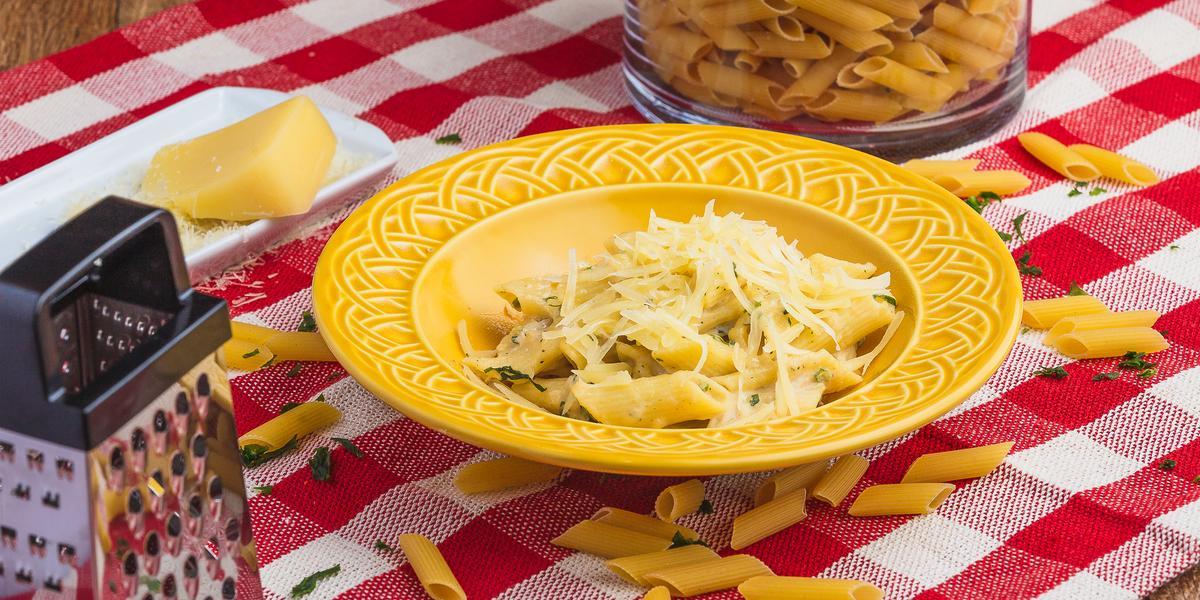 Foto de uma mesa com uma toalha xadrez vermelha e branca. Sobre ela há alguns macarrões crus, um ralador, um pedaço de queijo, um pote com mais macarrão e, ao centro, há um prato amarelo com a receita de Penne Alfredo.