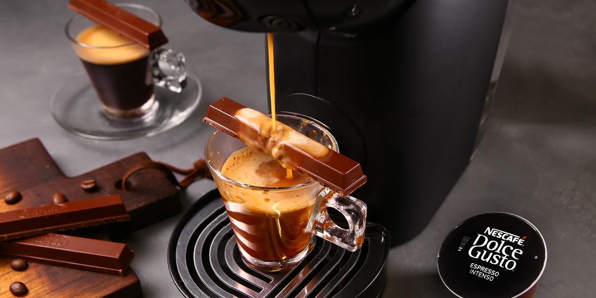 Fotografia em tons de preto em uma bancada de madeira cinza, uma máquina de Dolce Gusto com uma xícara de vidro e o café dentro dela, por cima, um KitKat sendo derretido pelo café caindo da máquina. Ao lado, tábua com gotas de chocolate.