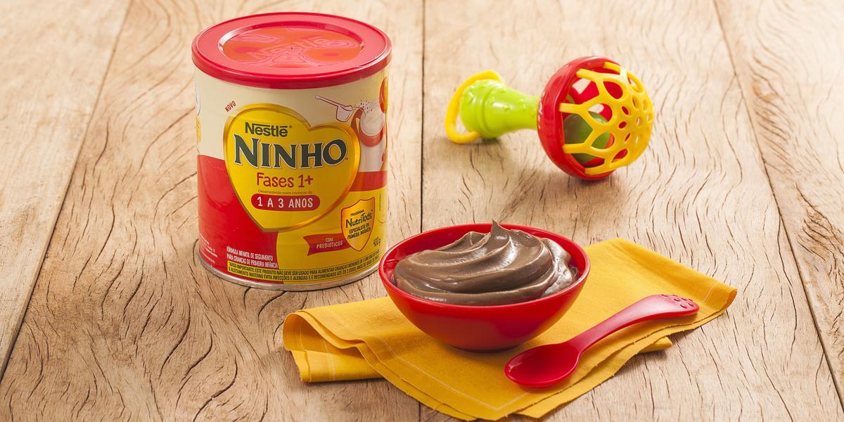 Fotografia em tons de amarelo e vermelho em uma bancada de madeira clara, um potinho vermelho em cima de um paninho amarelo, uma colher infantil vermelha e dentro do potinho um creminho de abacate com cacau. Ao fundo, brinquedinho e uma lata de Ninho Fase