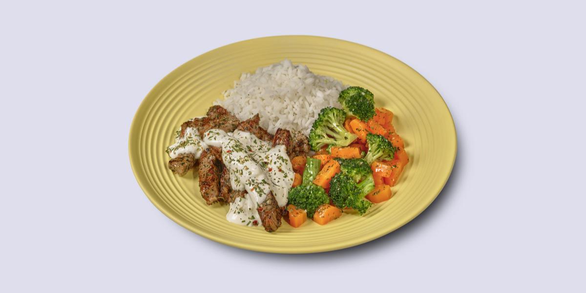 Fotografia em tons de amarelo em um fundo branco com um prato amarelo com arroz, legumes salteados e tirinhas de carne com molho de iogurte.