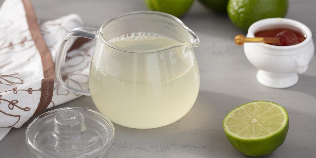 Fotografia em tons de verde em uma bancada cinza com um pano branco e detalhes marrom, uma chaleira de vidro com o chá de limão dentro. Ao lado, uma fatia do limão e um potinho com mel.