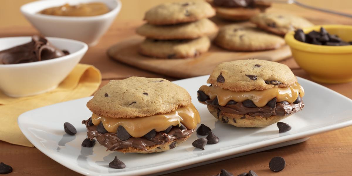 Fotografia em tons de amarelo em uma bancada de madeira com um recipiente branco ao centro com dois cookies recheados com doce de leite e creme de avelã. Ao fundo, potinhos com gotas de chocolate, doce de leite e uma tábua com mais cookies.
