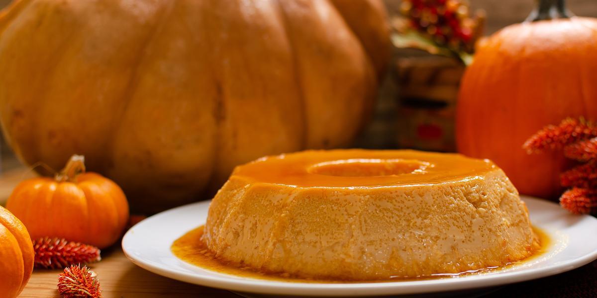 Fotografia em tons de laranja e branco de uma bancada de madeira marrom vista de frente, um prato branco redondo contém um pudim com calda por cima e ao redor. Ao fundo 4 abóboras de diferentes tamanhos.