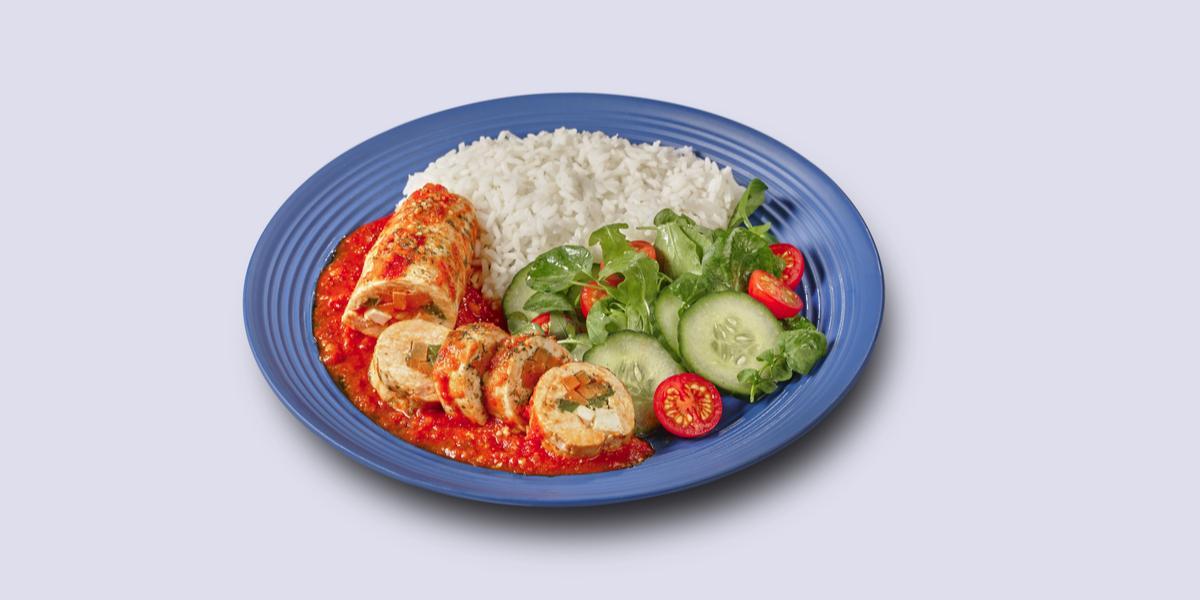 Fotografia em tons de azul em um fundo branco, ao centro um prato azul com arroz, salada verde e o filé de frango à rolê.