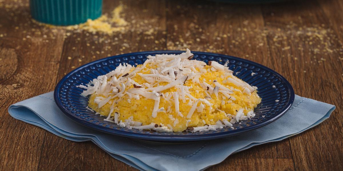 Imagem aproximada da receita de Cuscuz em tom amarelo, em um prato azul escuro, sobre um tecido em tom de azul claro. O cuscuz está decorado com coco ralado e, ao fundo, estão um pote com fubá amarelo e um outro prato com outro cuscuz