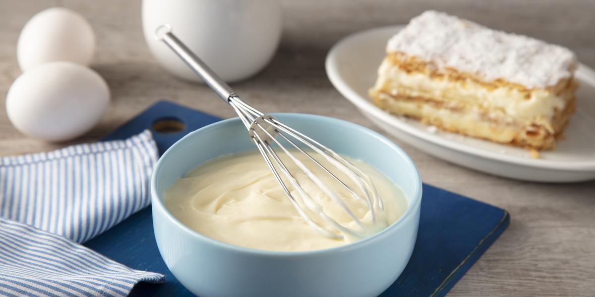 Fotografia em tons de azul em uma bancada de madeira, um pano azul listrado, uma tábua de madeira azul, um bowl azul claro com o creme belga dentro e um fouet. Ao lado, um prato com um pedaço de uma torta com o creme belga.