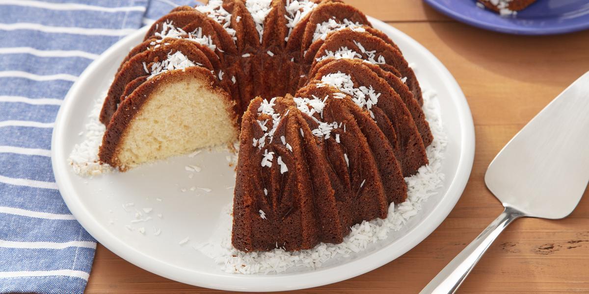 Fotografia em tons de marrom e azul de uma bancada de madeira, ao centro um prato branco e nele um bolo bem dourado por fora e branquinho por dentro. Ao lado uma pano azul com linhas brancas.