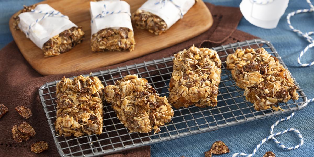 Fotografia em tons de marrom em uma bancada de madeira com uma toalha azul, um paninho marrom, uma tábua de madeira com três barrinhas de cereal em cima, um suporte de ferro quadriculado com quatro barrinhas de cereal em cima.