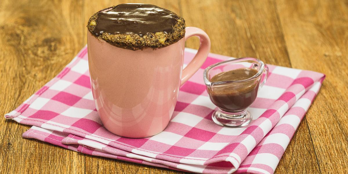 Fotografia em tons de rosa em uma bancada de madeira escura, um pano rosa xadrez, uma caneca rosa com um bolo de caneca de banana com mel, aveia e cobertura de chocolate. Ao lado, um potinho de vidro com a calda de chocolate.