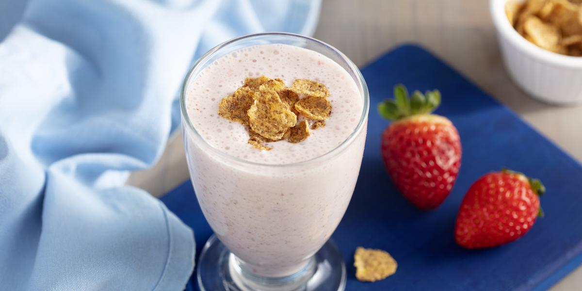 Imagem de um copo com a bebida em tom rosa claro, decorado com cereal por cima. Ele está sobre uma tábua azul escura e, ao redor, há um tecido azul claro, dois morangos e alguns cereais espalhados.