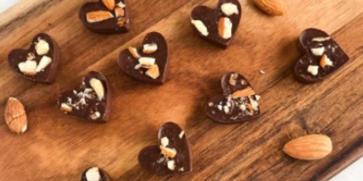 Fotografia em tons de marrom em uma bancada com uma toalha branca, uma tábua de madeira com vários docinhos de chocolate em formato de coração e amêndoas espalhadas pela tábua. Ao lado, uma colher com cabo de madeira e o chocolate endurecido na ponta.
