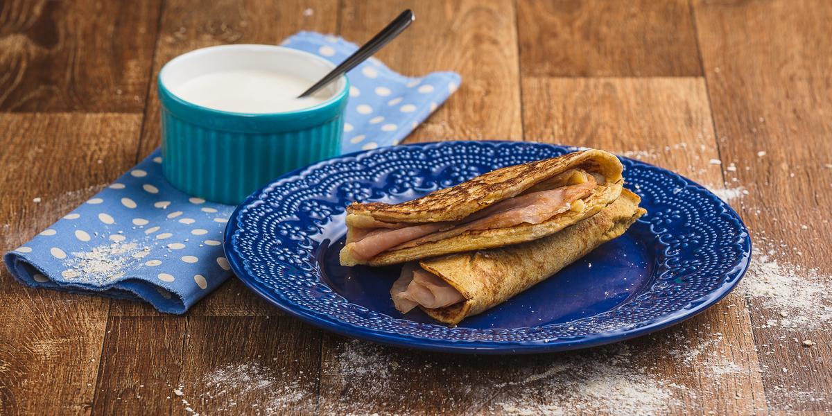 Imagem em tons de marrom e azul claro e escuro. No centro há um prato azul com duas quesadillas recheadas e, ao lado esquerdo, há um tecido azul com bolinhas brancas e, sobre ele, um pote azul com o creme azedo e uma colher.