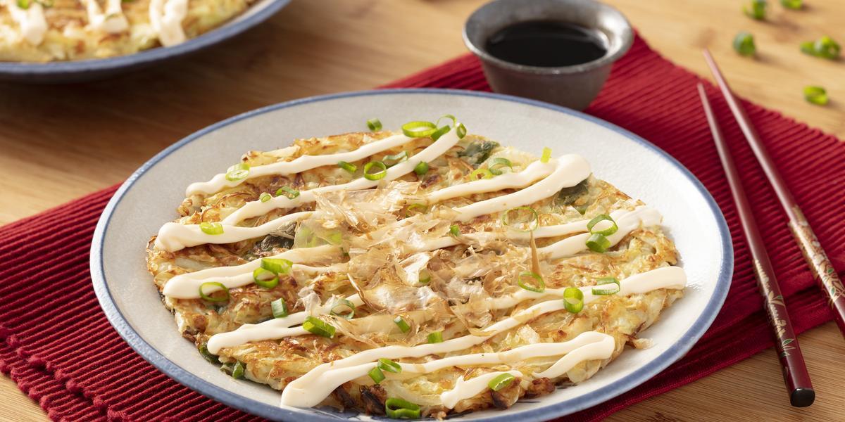 Fotografia em tons de vermelho em uma bancada de madeira com um jogo americano vermelho escuro, um prato branco com detalhes em azul ao centro com o okonomiyaki dentro dele e ao lado, um par de hashi. Ao fundo, um potinho com o molho de soja.
