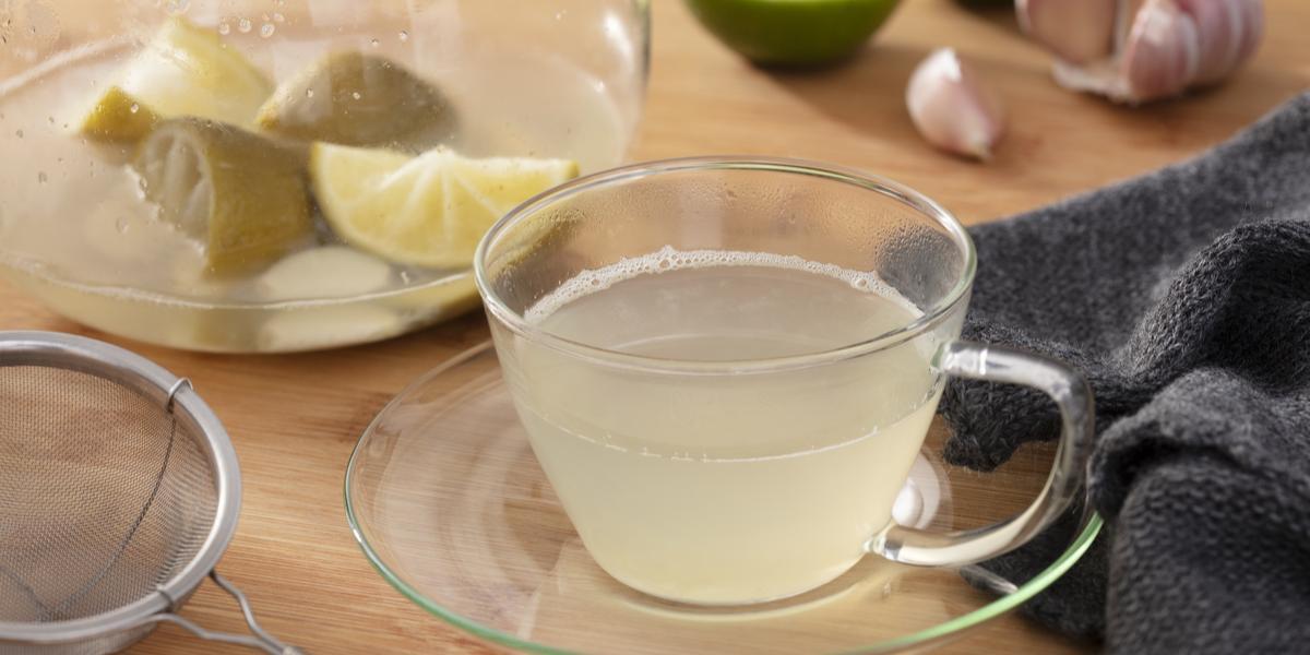 Fotografia em tons de verde em uma bancada de madeira, um pano cinza escuro, um prato de vidro pequeno com uma xícara e o chá de limão com alho dentro dele. Ao fundo, limão e alho espalhado pela mesa.