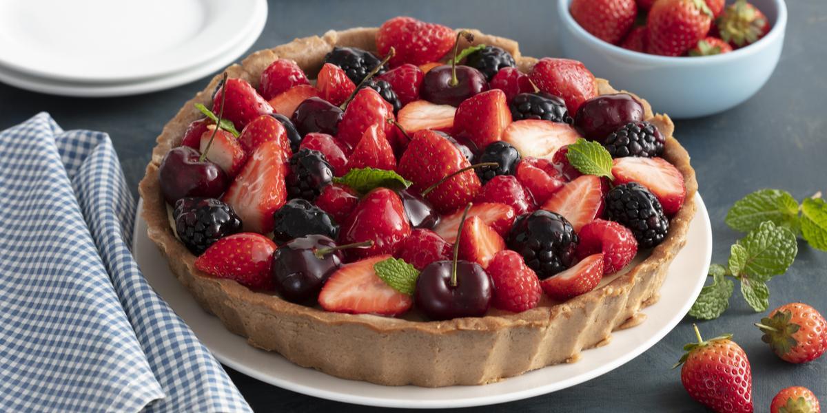 Fotografia em tons de vermelho e azul de uma bancada, ao centro a torta com morango, amoras e cerejas. Ao lado um pano quadriculado azul e branco e morangos.