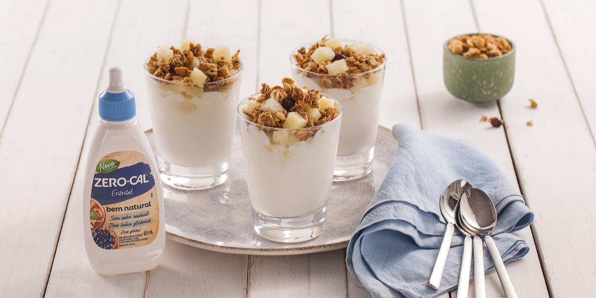 Fotografia em tons de azul em uma bancada de madeira clara, um paninho azul, um prato redondo com três copinhos de vidro com a sobremesa gelado de abacaxi com granola. Ao lado, um tubo de adoçante Zero-Cal e um potinho com granola.