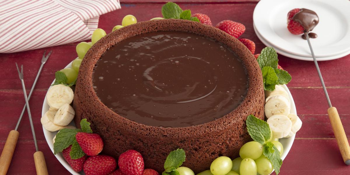 Fotografia em tons de vermelho em uma mesa de madeira vermelha com um prato branco ao centro e o bolo fondue em cima, em volta, morangos, uvas e bananas. Ao lado, garfinhos de fondue e um paninho listrado vermelho.