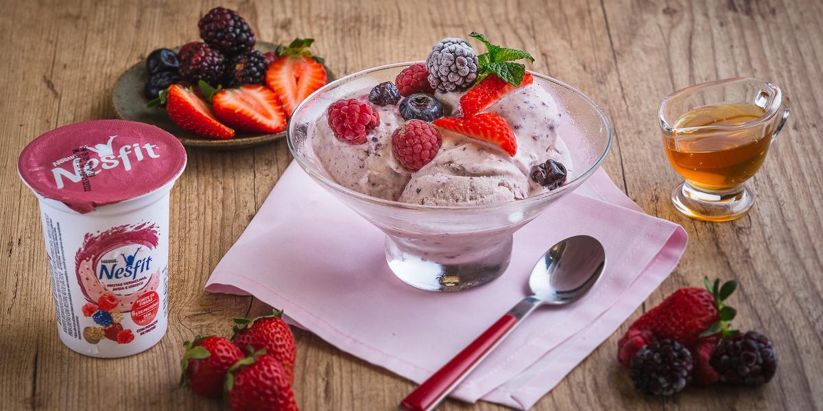 Fotografia em tons de rosa em uma bancada de madeira clara, um pote de vidro com o sorvete de frutas vermelhas, ao lado um potinho com mel e um pratinho com frutas vermelhas.