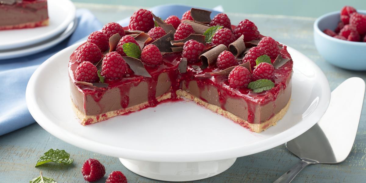 Fotografia em tons de vermelho em uma bancada de madeira azul, um pano azul claro, um suporte para bolo branco com a cheesecake de chocolate com calda de framboesa em cima do suporte, decorado com raspas de chocolate e framboesas.