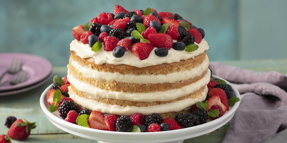 Fotografia em tons de vermelho e lilás em uma bancada de madeira verde, um pano roxo, um suporte para bolo com o bolo pelado (naked cake) com creme branco e com decoração de frutas vermelhas. Ao fundo, pratos pequenos lilás de sobremesa.