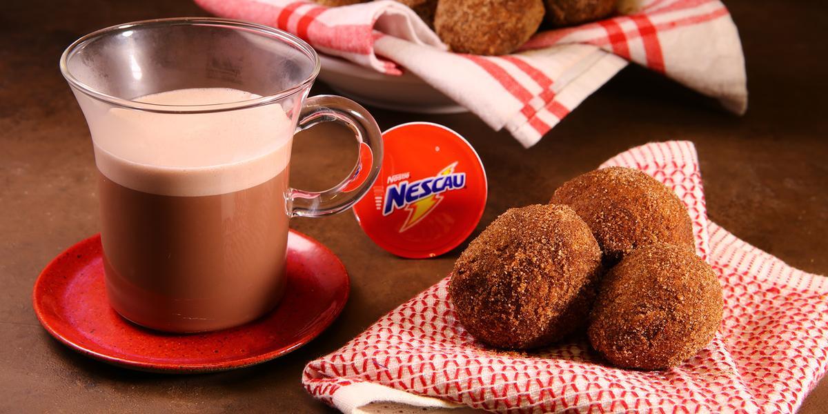 Fotografia em tons de vermelho em uma bancada de madeira escura, um pano vermelho com três bolinhos de chuva de café e chocolate em cima. Ao lado, um pratinho vermelho pequeno redondo com uma xícara de vidro com o Café Nescau dentro.