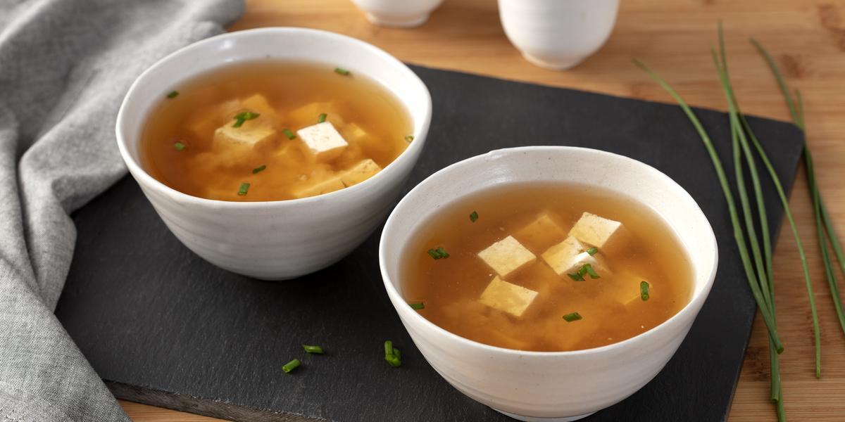 Fotografia em tons de marrom em uma bancada de madeira clara com uma tábua de madeira preta ao centro e dois pratos redondos e fundos com a sopa missoshiro dentro. Ao lado, talos de cebolinha.