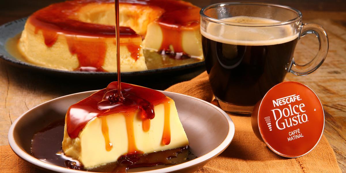 Fotografia em tons de laranja em uma bancada de madeira escura, um pano laranja, um prato redondo marrom com uma fatia de pudim de leite com calda de caramelo. Ao lado, uma xícara de vidro com o café matinal. Ao fundo, um prato maior com o pudim inteiro.
