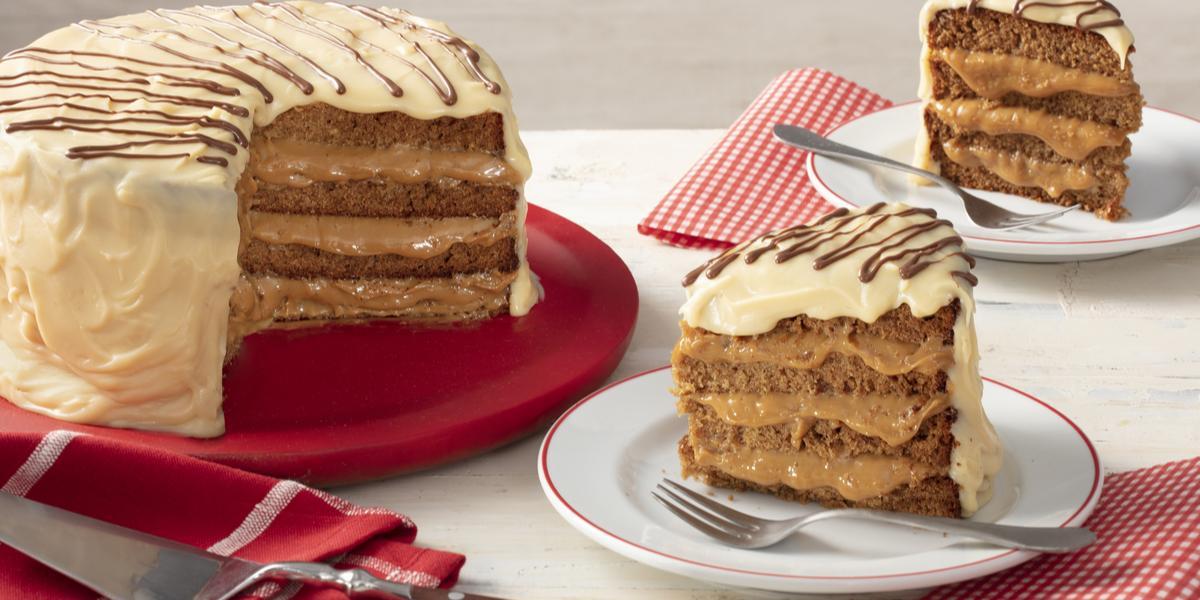 Fotografia em tons de vermelho em uma bancada cinza com paninhos vermelhos listrados e de bolinhas brancas. Ao centro, um prato branco com uma fatia do bolo de pão de mel com chocolate branco e à esquerda, um suporte grande vermelho com o bolo inteiro.