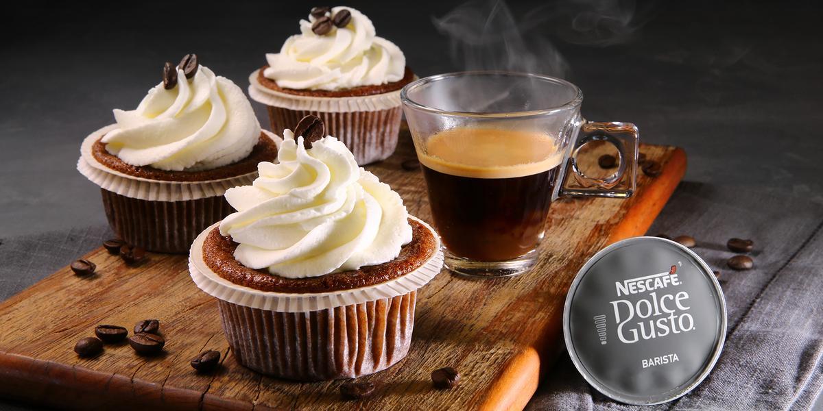 Fotografia em tons de marrom em uma bancada cinza com pano cinza escuro, uma tábua de madeira com três forminhas com cupcakes feitos com café e leite dentro delas. Ao lado, uma xícara de café e a cápsula do Café Barista Dolce Gusto.